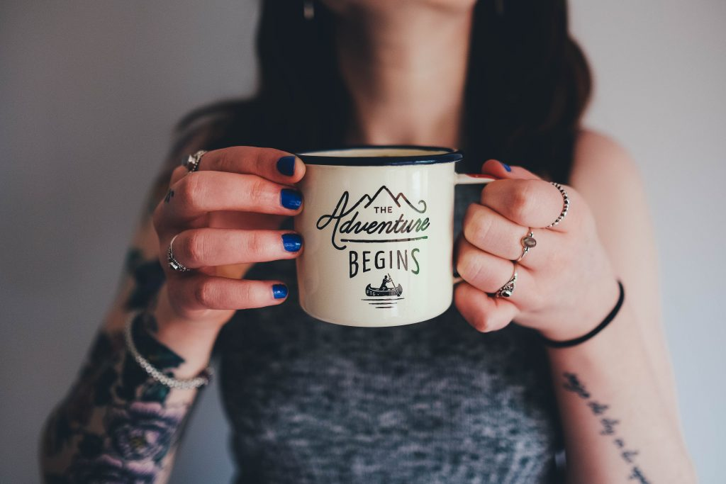 "Woman's hands holding a mug that says ""the adventure begins."""
