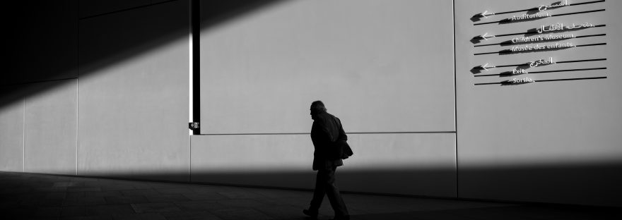 Black and white photo of a man walking alone in silhouette.