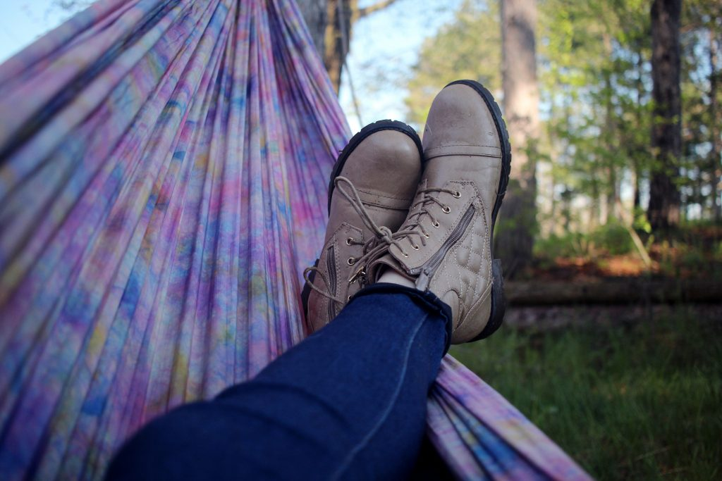 Lower legs wearing blue jeans and brown boots in a tie-died hammock.