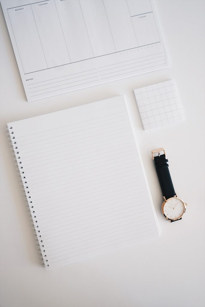Blank notebook page, planner and stikcy notes beside a watch with a black band and white face; wasting time
