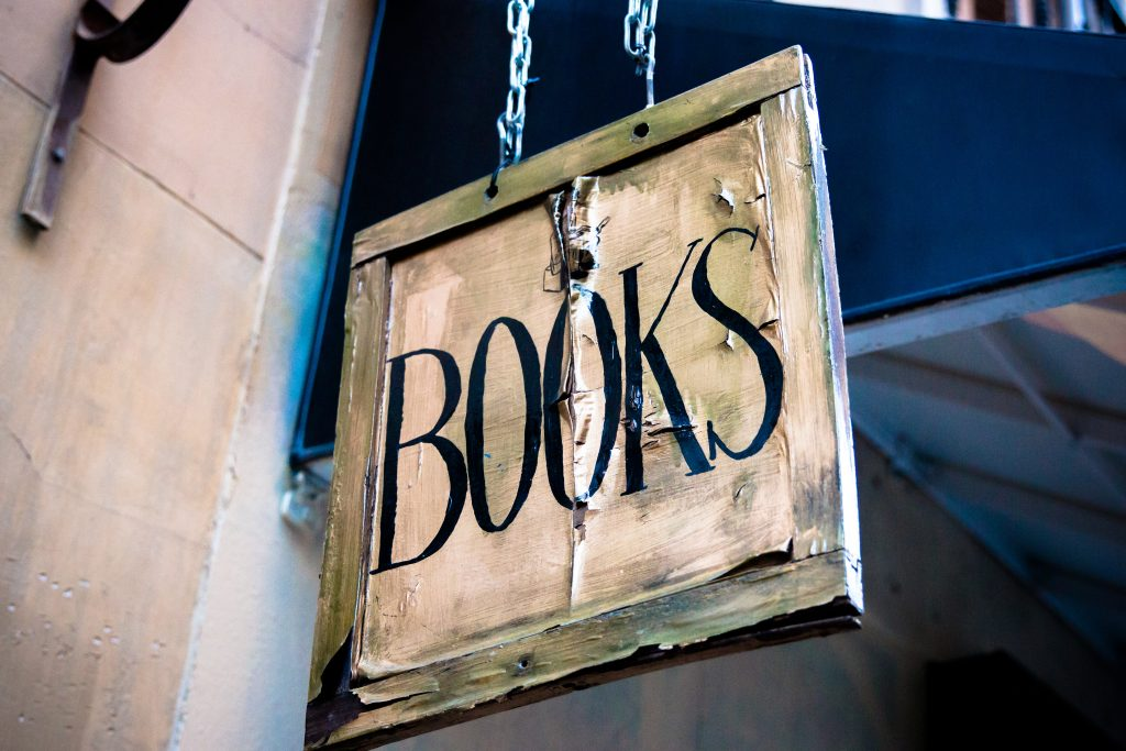 "Old hanging sign that says ""BOOKS""."