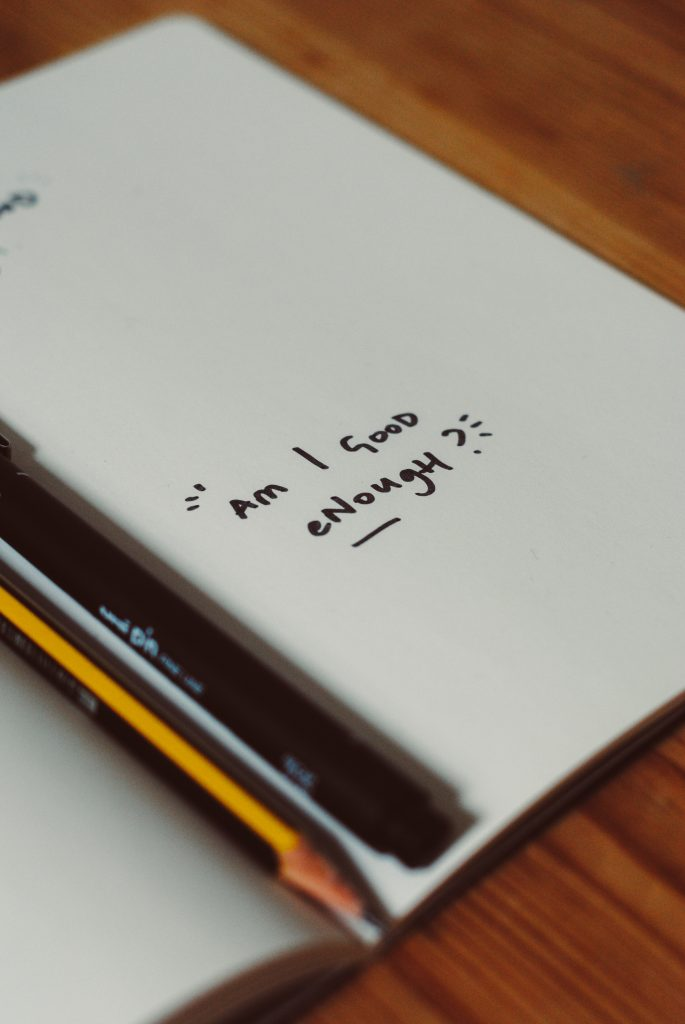 "Notebook with the words ""Am I good enough?"" in handwriting on a blank page."
