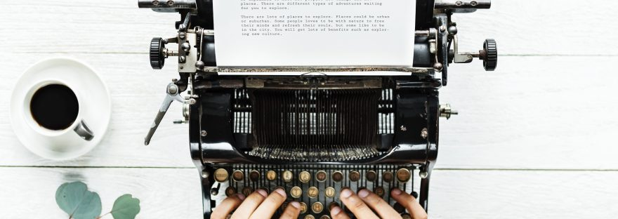 Hands poised over an old typewriter with typed page coming out.