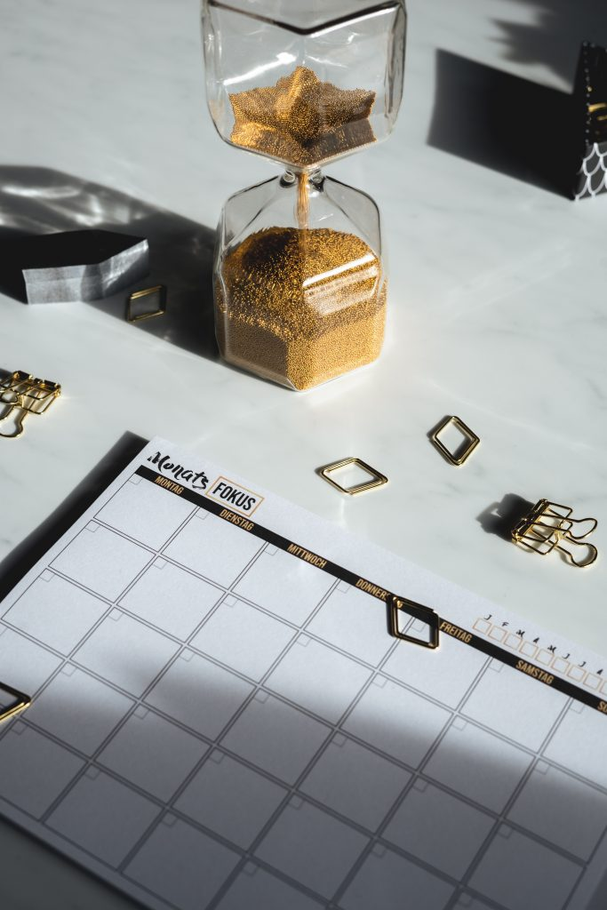 Hourglass with golden sand next to a monthly calendar page.