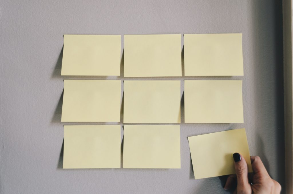 Nine yellow post it notes on a gray wall with a hand adding the ninth.