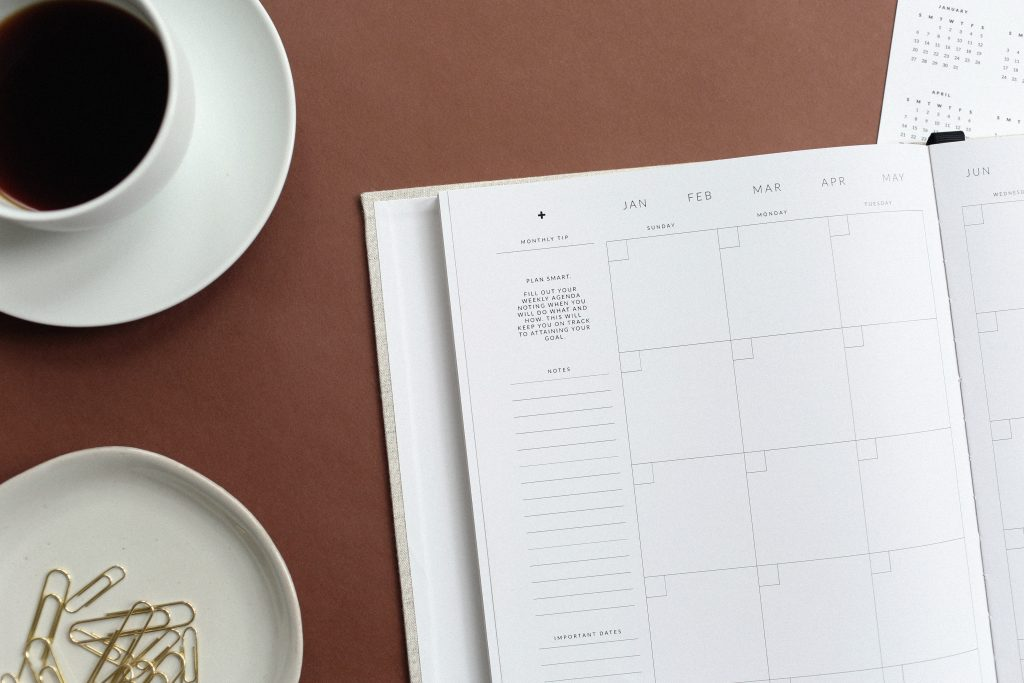 Blank calendar page in a day planner beside cup of coffee and saucer of gold paper clips.