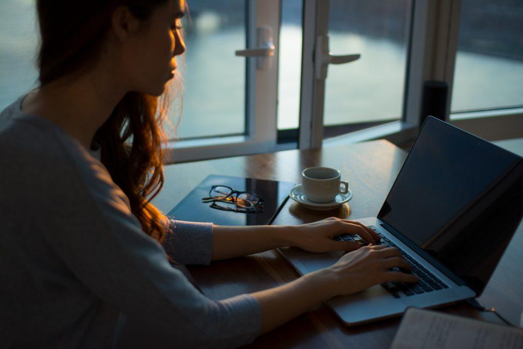 Women typing on macbook beside an open window in dusk light.