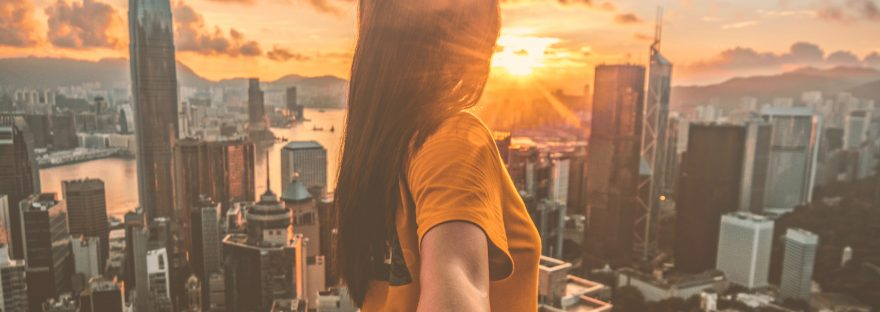Person standing on ledge looking a city with a sunset