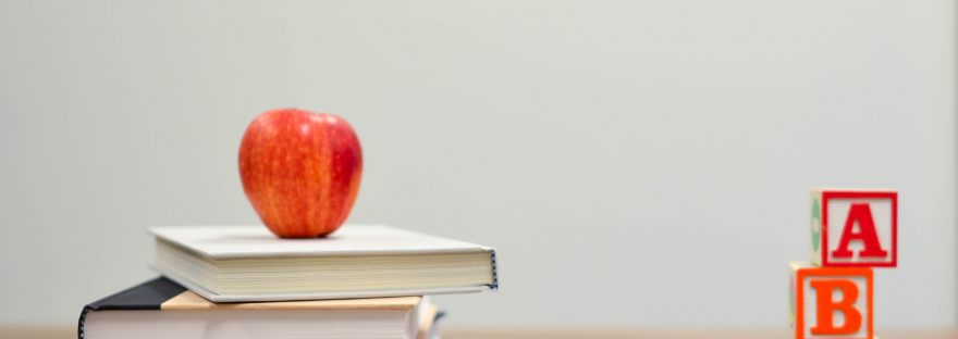 red apple on a stack of four books