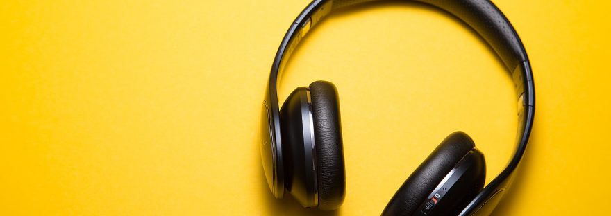 Black over ear headphones lying on a yellow background
