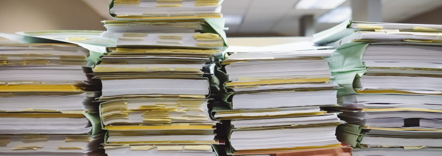 Stacks of paper folders with yellow post it notes